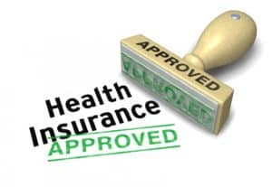 "a wooden stamp in green ink indicating ""Health Insurance Approved"""