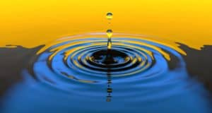 a drop of water lands in a smooth body of vibrant blue water with a vibrant color of golden horizon in the background